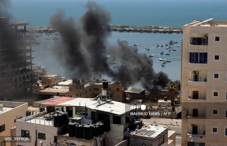 Columnas de humo negro se elevan durante un ataque aéreo israelí en el puerto marítimo de la ciudad de Gaza