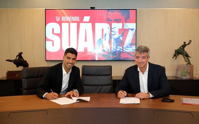 Luis Suárez (i) firma contrato con el Atlético de Madrid, en compañía del consejero delegado del club, Miguel Ángel Gil (d)
